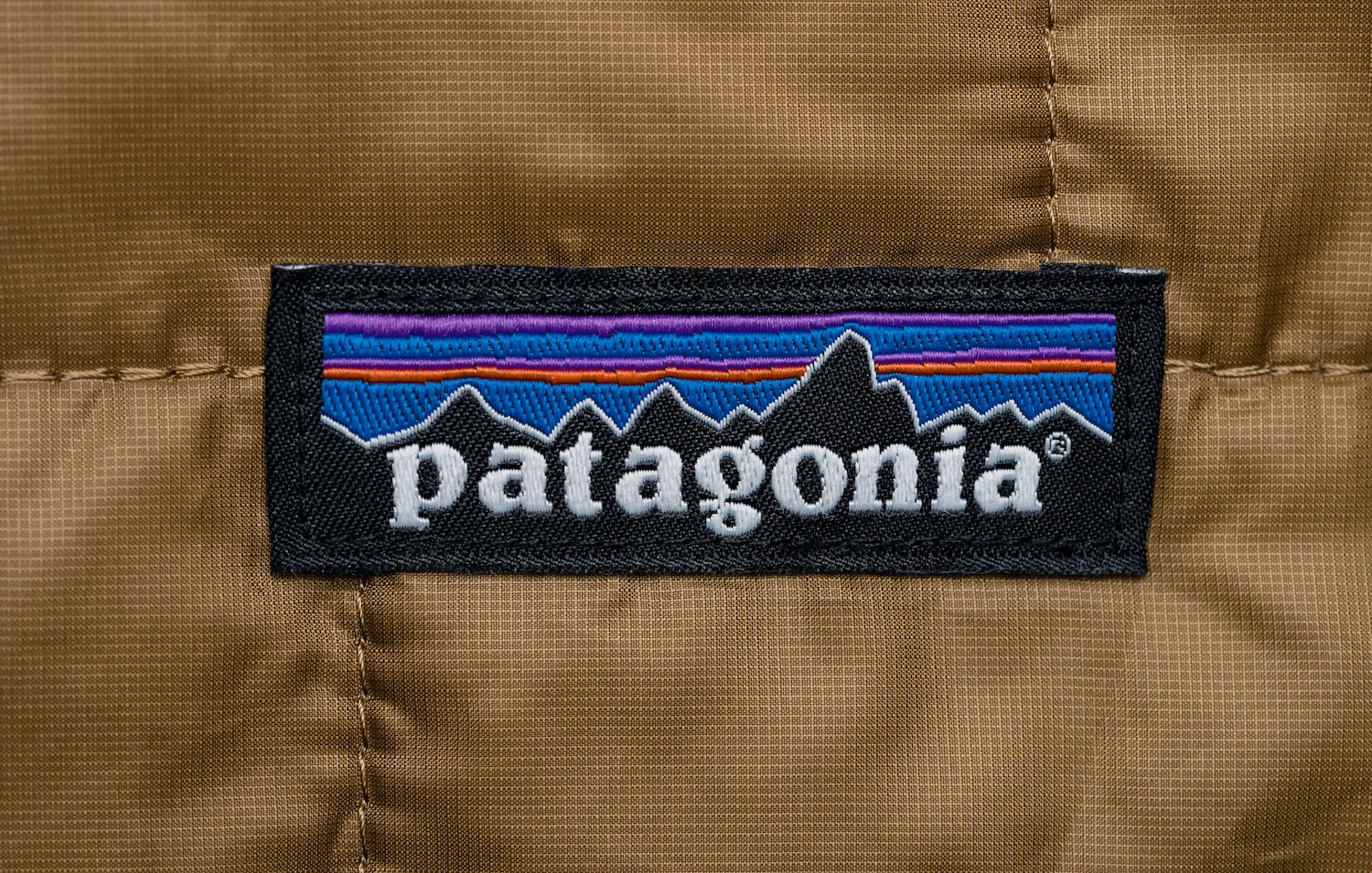A brown jacket with a Patagornia logo embroidered on the front
