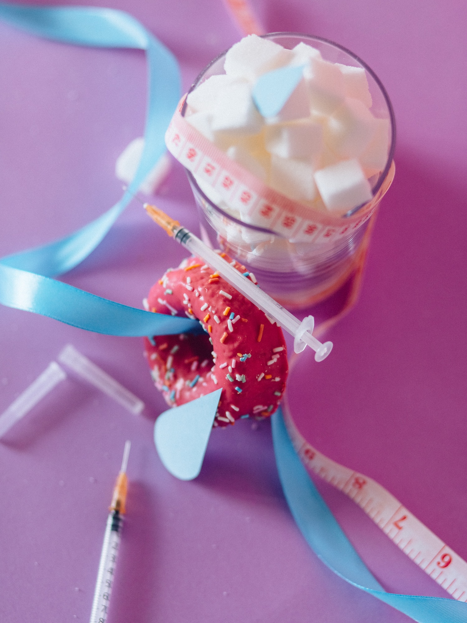A cup of sugar, a donut, and insulin pens showing the dangers of sugar and diabetes