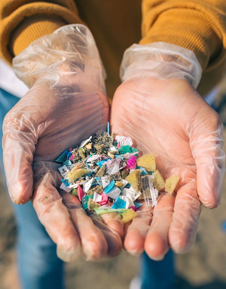 Detail of hands showing microplastics on the beach